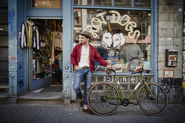 Germany, Hamburg, St. Pauli, Man with bicycle waiting in front of vintage shop