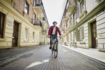 Germany, Hamburg, St. Pauli, Man riding bicycle in he city