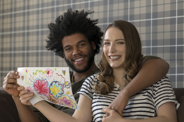 Smiling couple sitting on couch showing children's drawing