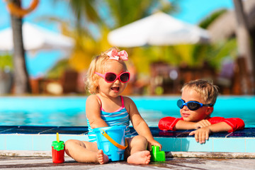 little boy and girl playing in swimming pool at beach