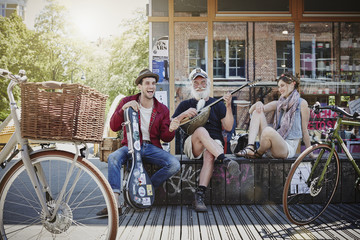 Germany, Hamburg, St. Pauli, Couple listening to old sailor, making street music