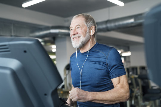 Fit senior man on treadmill working out in gym