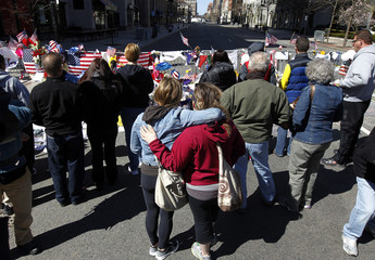 Sarah Orr hugs her sister Heather at a memorial to the victims of the Boston Marathon bombings near the scene of the blasts on Boylston Street in Boston
