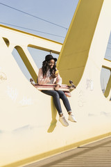 Young woman sitting on  bridge using smartphone