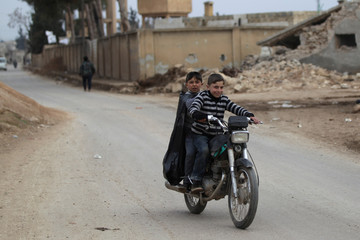 Boys ride a motorcycle near rubble of damaged buildings in al-Rai town