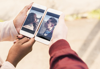 Hands holding smart phones with pictures of a young couple