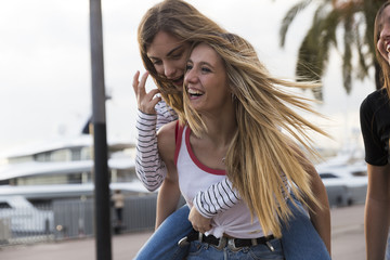 Laughing young woman giving her friend a piggyback ride
