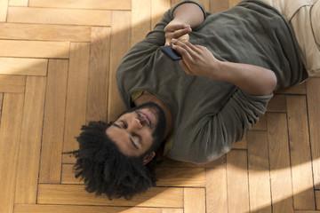 Man lying on floor with smartphone