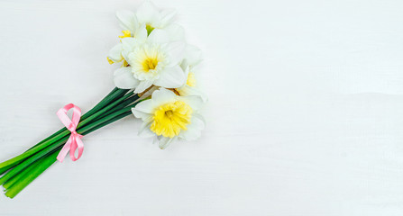 Bright yellow daffodils in vase on white wooden table with copy space. Yellow and white narcissus. Greeting card. Top view