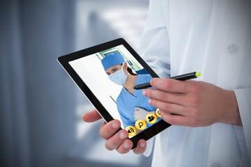 Composite image of doctor using digital tablet