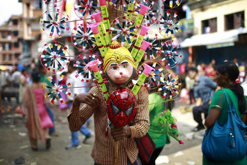 A vendor selling toys waits for customer during the chariot festival of Rato Machhindranath in Lalitpur