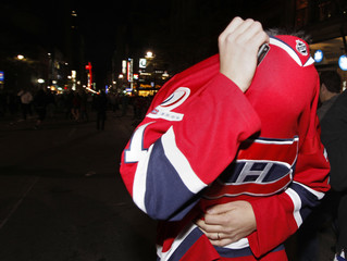 A Canadiens fan covers his face after police fired tear gas as fans celebrate their team's win over the Penguins in the NHL Eastern Conference semi-final hockey series in downtown Montreal