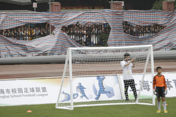 Fans of former England captain David Beckham wait for him to enter a soccer field at Tongji University in Shanghai