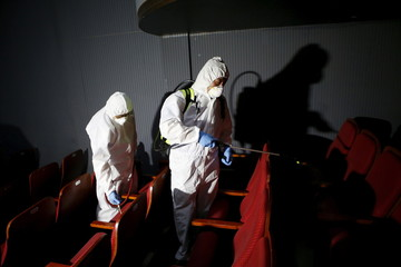 Employees from a disinfection service company sanitize the interior of a theater in Seoul