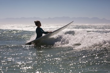 Female surfer surfing in the sea with surfboard