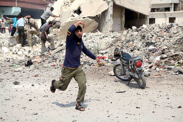 A man reacts as he runs at a site hit by what activists said was a barrel bomb dropped by forces loyal to Syria's President Bashar al-Assad, followed by shelling at a bus station in Jisr al-Hajj roundabout in Aleppo