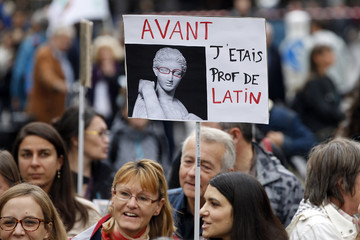 """A striking French teacher holds up a placards which reads """"Before I was a Latin teacher"""" as she takes part in a nation-wide protest against new measures aimed at revamping the country's school system in Paris"""