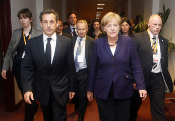 France's President Sarkozy and Germany's Chancellor Merkel walk together during a Euro Zone leaders summit in Brussels