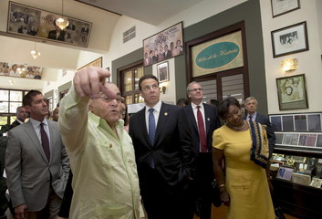 Martinez shows Cuomo the bar of the hotel decorated with celebrity pictures before meetings in Havana
