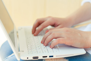 Woman working at home hand on keyboard close up. Girl typing on laptop.