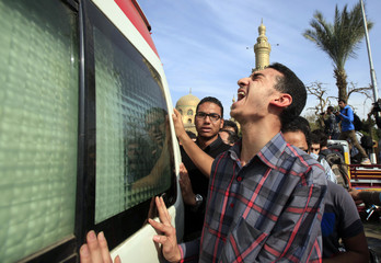A friend of Mohamed Reda cries at the vehicle transporting his coffin during his funeral service at Al Sayyida Nafisa mosque in Cairo