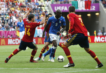 Italy's Balotelli is challenged by Spain's Alonso and Pique during their Group C Euro 2012 soccer match at PGE Arena in Gdansk