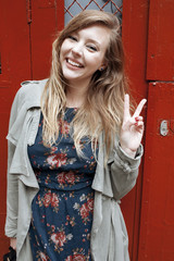 Portrait of smiling young woman doing v sign