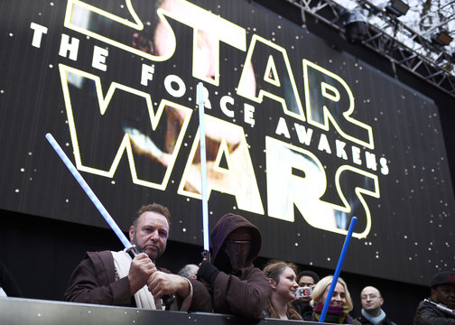 Enthusiasts wave toy light sabres as they wait to spot members of the cast at the European Premiere of Star Wars, The Force Awakens in Leicester Square, London