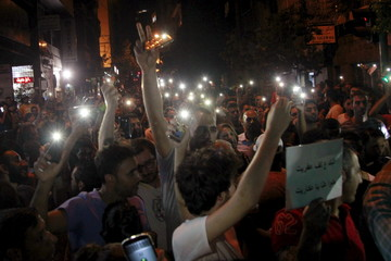 People hold up lit candles and mobile phones during a vigil to express solidarity with a protester who was injured during clashes with police on Sunday, outside AUB hospital in Beirut, Lebanon
