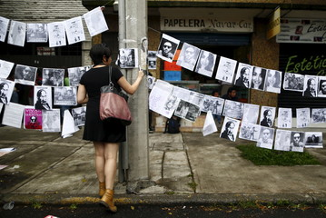 A demonstrator hangs pictures during a demonstration against the murder of photojournalist Ruben Espinosa and four other women outside the building where the bodies were found in Mexico City