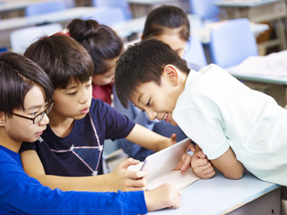 asian schoolchildren using digital tablet together