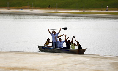 Rio de Janeiro Mayor Eduardo Paes, accompanied by guests, holds a rowing stick as he greets media, during the presentation of the Rio 2016 Olympic Games' Slalom Canoe Circuit, which is part of the X-Park, at the Deodoro Sports Complex in Rio de Janeiro