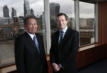 Nikkei Chairman Tsuneo Kita and Financial Times CEO John Ridding pose for a photo at the Financial Times headquarters in London