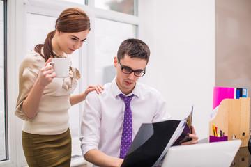 Young office workers look at opened folder at the office