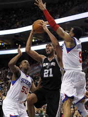 Spurs' Duncan shoots under pressure from the Philadelphia 76ers' Allen and Iguodala during their NBA basketball game in Philadelphia