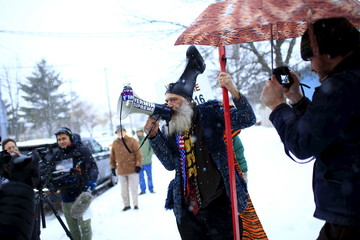 Vermin Supreme talks through a bullhorn at the bus carrying U.S. Republican presidential candidate Ted Cruz at a campaign event in Manchester