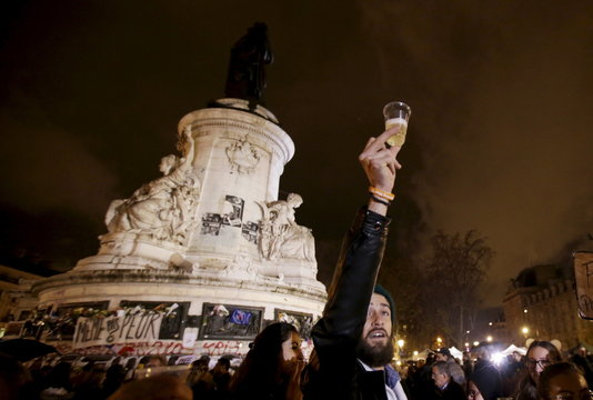 "A man holds a glass of champaign on the ""Republique"" square in Paris"