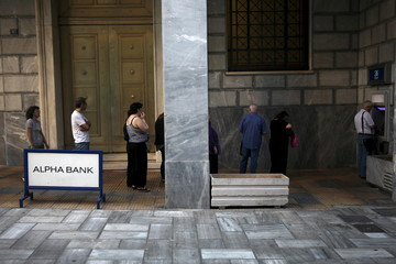 People line up at an ATM outside an Alpha Bank branch in Athens, Greece