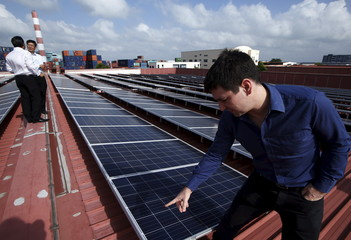 Sun Electric's Chief Executive Officer Matthew Peloso speaks next to rows of rooftop solar panels operated under the company's SolarSpace energy retail programme at a factory in Singapore