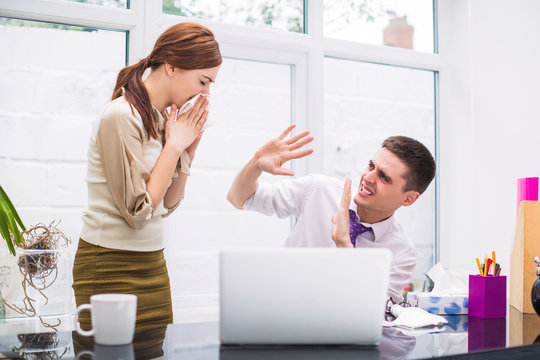Young sick office worker stands near her colleague at the office and wipes nose