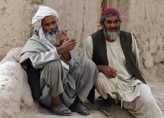 Two Afghan men sit along a street in the village of Loy Bala Karz southeast of Kandahar City
