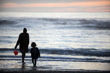 Mutter und kind  spielen in der Abendsonne am Meer