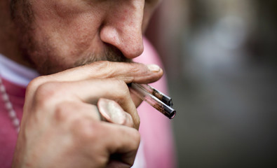 A man holds his used crack pipes in his mouth in Vancouver's DTES neighbourhood