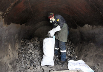 A worker fills a bag with charcoal inside a furnace at a charcoal production site in the village of Oslivka