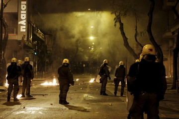 Riot police stand guard during clashes with hooded youth seen in Athens