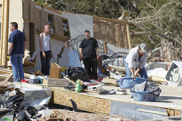 Family members salvage what they can from the remains of the home where their mother died near Crossville, Tennessee