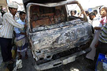 Anti-government protesters look at a burnt truck during clashes between security forces and opposition fighters in Taiz