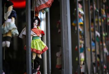 Little handmade dolls hang outside the window of a restaurant in the Santa Teresa neighborhood of Rio de Janeiro