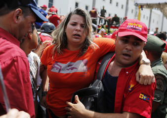 A woman is carried out of the crowd of supporters of Venezuela's late President Hugo Chavez in Caracas