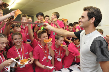 Switzerland's Federer hands out slices of pizza to the tournament's ball boys and girls after he won the Swiss Indoors ATP tennis tournament in Basel